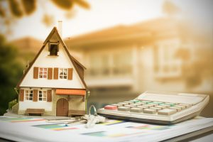 small home beside calculator