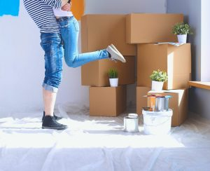 two young adults standing in front of moving boxes in their first Kelowna home