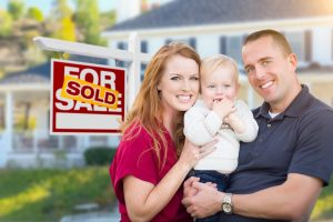 couple holding son in front of home with moving sign