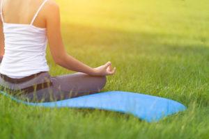 lady sitting on lawn doing yoga