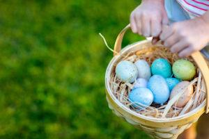girl holding basket full of Easter eggs