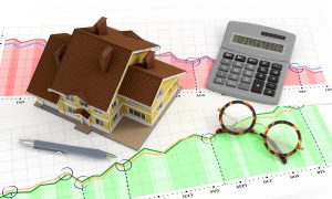 small toy home and calculator on a graph