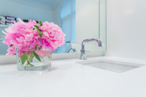 glass jar with flowers in bathroom on counter