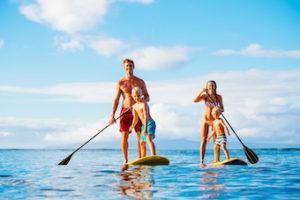 family paddleboarding on lake